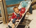 Della in push chair by the sea in Bude, July 1985