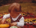 Debbie playing outside on a blanket 1980