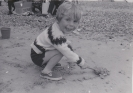 Freda's young son Chris playing with sand on beach